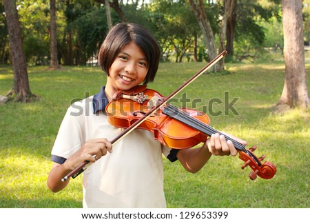 Happy young girl plays her  violin - stock photo