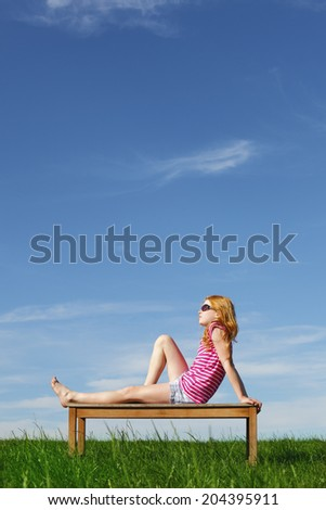 Happy young girl posing outdoors on an bench - stock photo