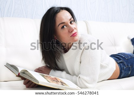 Happy young girl reading a book on the couch.
