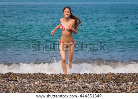 Happy young girl running from sea on beach with pebbles - stock photo