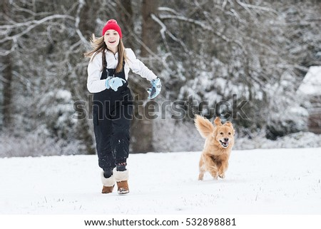 Happy young girl running in the snow with her golden retriever d