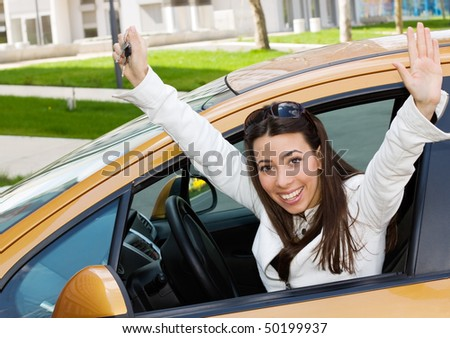 Happy  young girl sitting in a new car with raised hands - stock photo