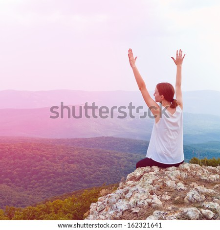 Happy young girl sitting on a cliff side. Young woman relaxing in mountains at sunrise - stock photo