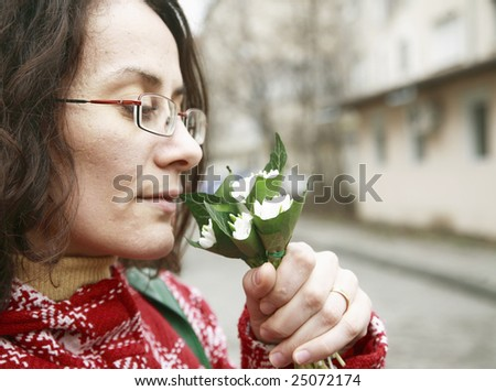 Happy Young Girl Smelling Snowdrop - stock photo