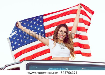 Happy Young Girl Standing In Convertible Car Holding Waving American USA Flag For Independence Day. Selective Focus.