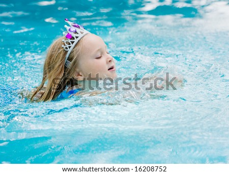 Happy young girl swimming with a crown