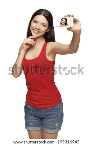 Happy young girl taking pictures of herself through cell phone, over white background - stock photo