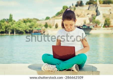 Happy young girl using laptop outdoors - stock photo