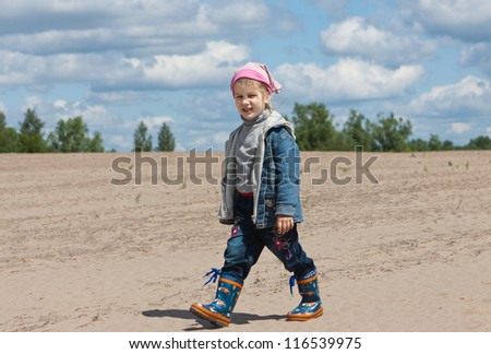 happy young girl walking on empty field