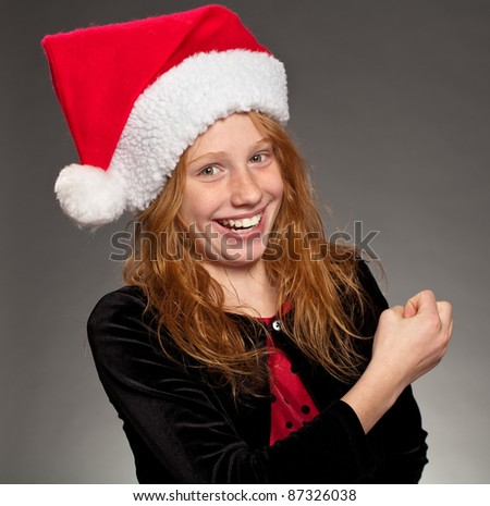 Happy young girl wearing a Santa hat - stock photo