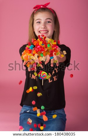 Happy young girl with a handful of colorful candy. - stock photo