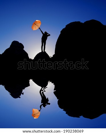 Happy young girl with an umbrella at sunset  - stock photo