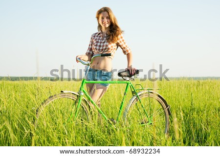 Happy young girl with  bicycle in grass meadow - stock photo