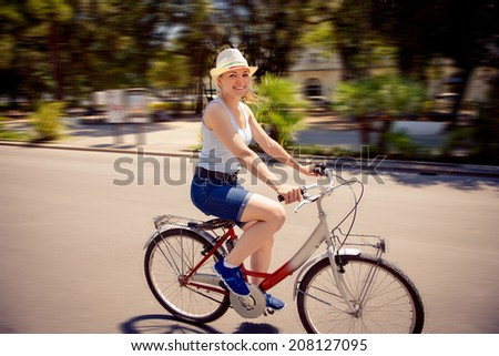 Happy young girl with bicycle in town