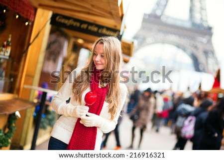 Happy young girl with caramel apple on a Parisian Christmas market with the Eiffel tower in the background - stock photo