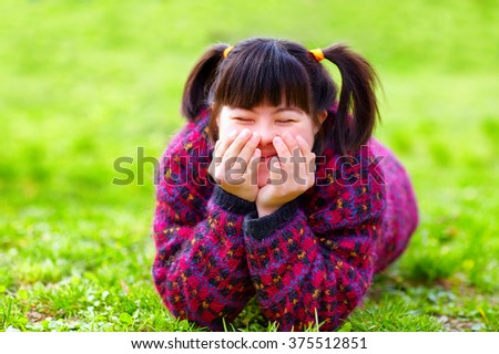 happy young girl with disability on spring lawn - stock photo