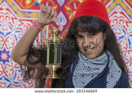 Happy Young Girl with Fez and Lantern Celebrating Ramadan over Ramadan Fabric - stock photo