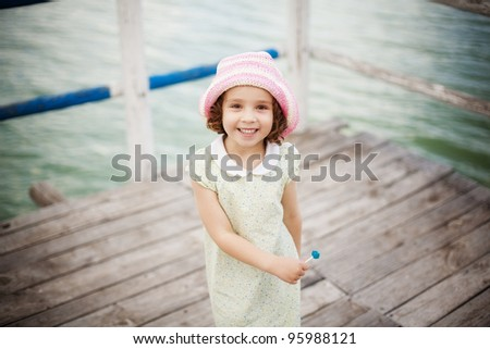 Happy young girl with lolly-pop on a pier - stock photo