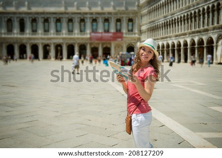 Happy young girl with map at San Marco square in Venice  - stock photo