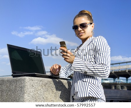 happy young girl with mobile telephone and laptop on the street