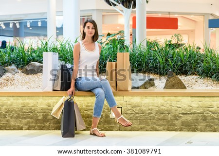 Happy Young Girl With Shopping Bags Taking A Break In Shopping Mall - stock photo