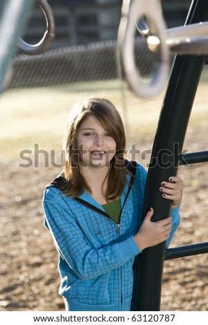 Happy young girl (11 years) standing by playground equipment