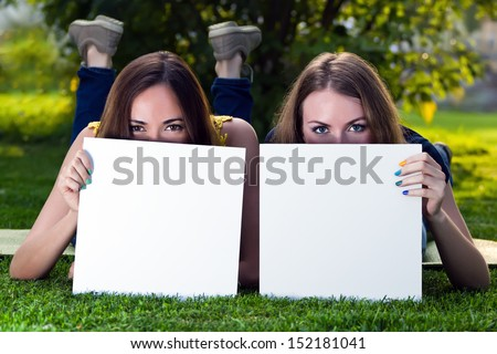 Happy young girls holding white blank papers against background of summer green park. Young girls showing blank boards. Female models portrait outside. - stock photo