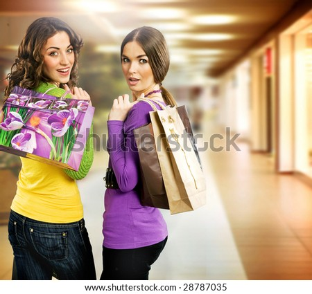 Happy young girls in shopping center - stock photo