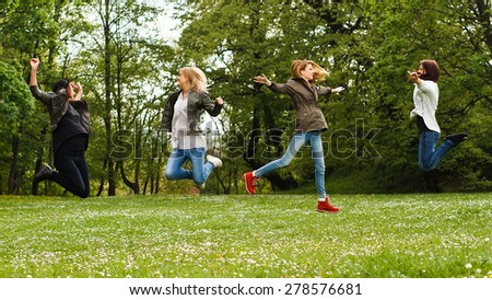 Happy young girls jumping in the park.Happy girls - stock photo