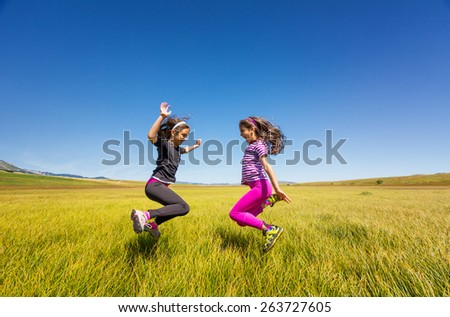 Happy young girls jumping on a meadow. Cheerful girls jumping on a meadow. - stock photo