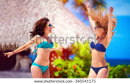 happy young girls jumping on tropical beach, summer vacation - stock photo