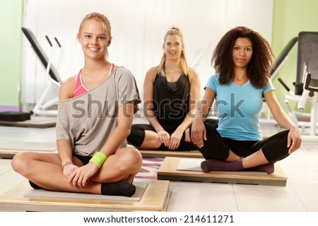 Happy young girls resting at the gym, smiling. - stock photo
