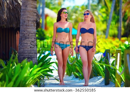 happy young girls walking on tropical beach, during summer vacation
