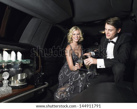 Happy young glamorous couple enjoying champagne in limousine - stock photo