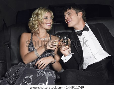 Happy young glamorous couple toasting champagne in limousine - stock photo