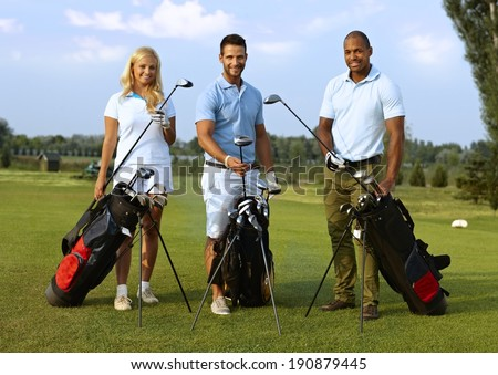 Happy young golfers standing on golf course, smiling, looking at camera. - stock photo