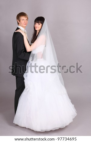 Happy young groom and beautiful bride embrace and look at camera in studio on gray background - stock photo