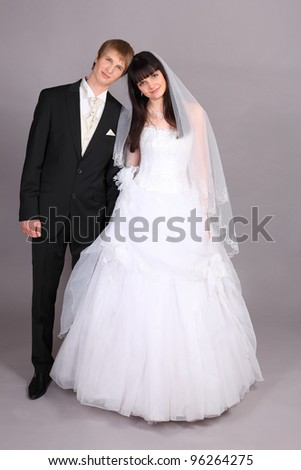Happy young groom and beautiful bride stand and connected heads in studio on gray background - stock photo
