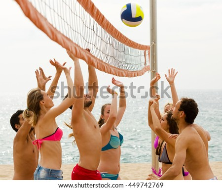 Happy young group of friends having fun at beach and playing ball - stock photo