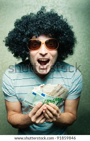 Happy young guy in afro curly wig with eyeglasses holding lots of money - stock photo