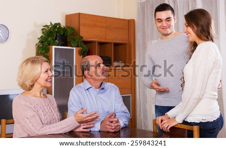 Happy young guy showing his future wife to smiling parents - stock photo
