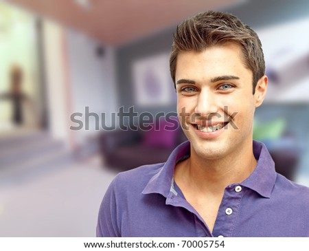 Happy young handsome man at home - stock photo