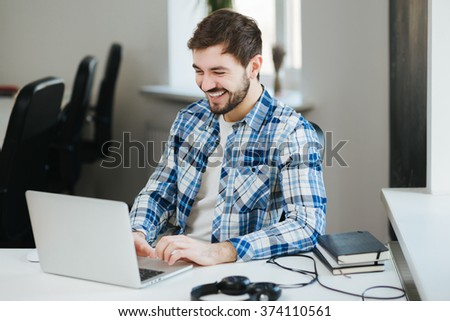 Happy young handsome man wearing casual shirt working on laptop in office and smiling - stock photo