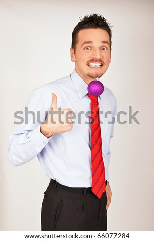 Happy young has violet Christmas Ornament between teeth and shows with thumb yes. - stock photo