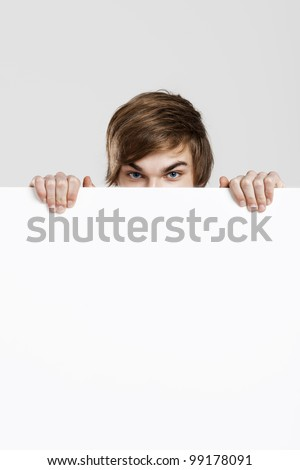 Happy young hiding and peeking behind a blank white card - stock photo