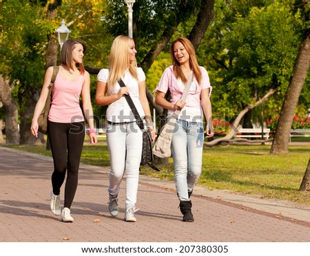 happy young high school students or college girls smiling walking to school through the park/happy young high school students - stock photo