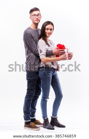 Happy young hipster couple  hugs with present posing at camera isolated on a white background. Happy man giving a gift to his girlfriend. Holiday. - stock photo