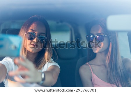 Happy young hipster woman holding smartphone and taking selfies in car - stock photo