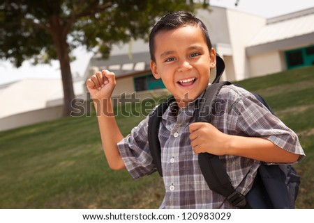 Happy Young Hispanic Boy with First in the Air Wearing Backpack Ready for School. - stock photo