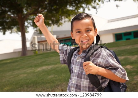 Happy Young Hispanic Boy with First in the Air Wearing Backpack Ready for School.